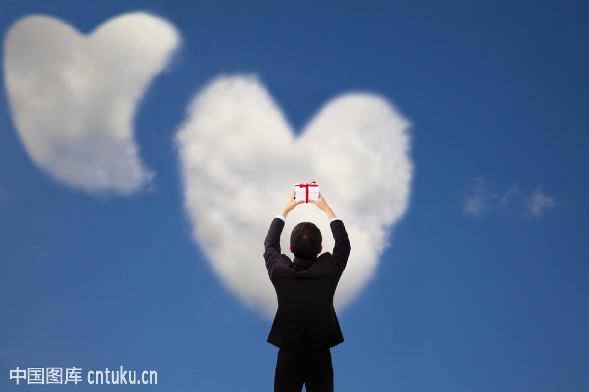 男人拿礼物,两颗心和爱情云图片