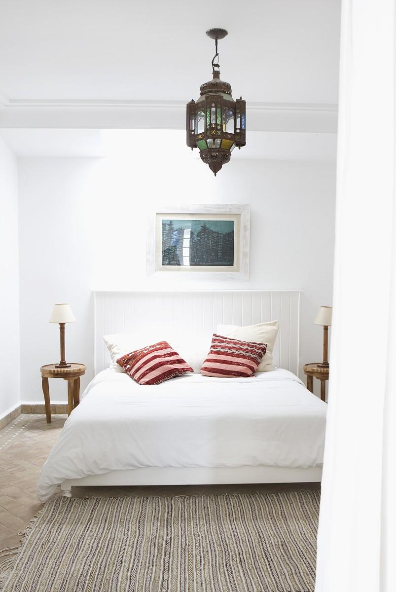随着木板的床头板和明亮的散射垫东方吊灯下面简单的床图片