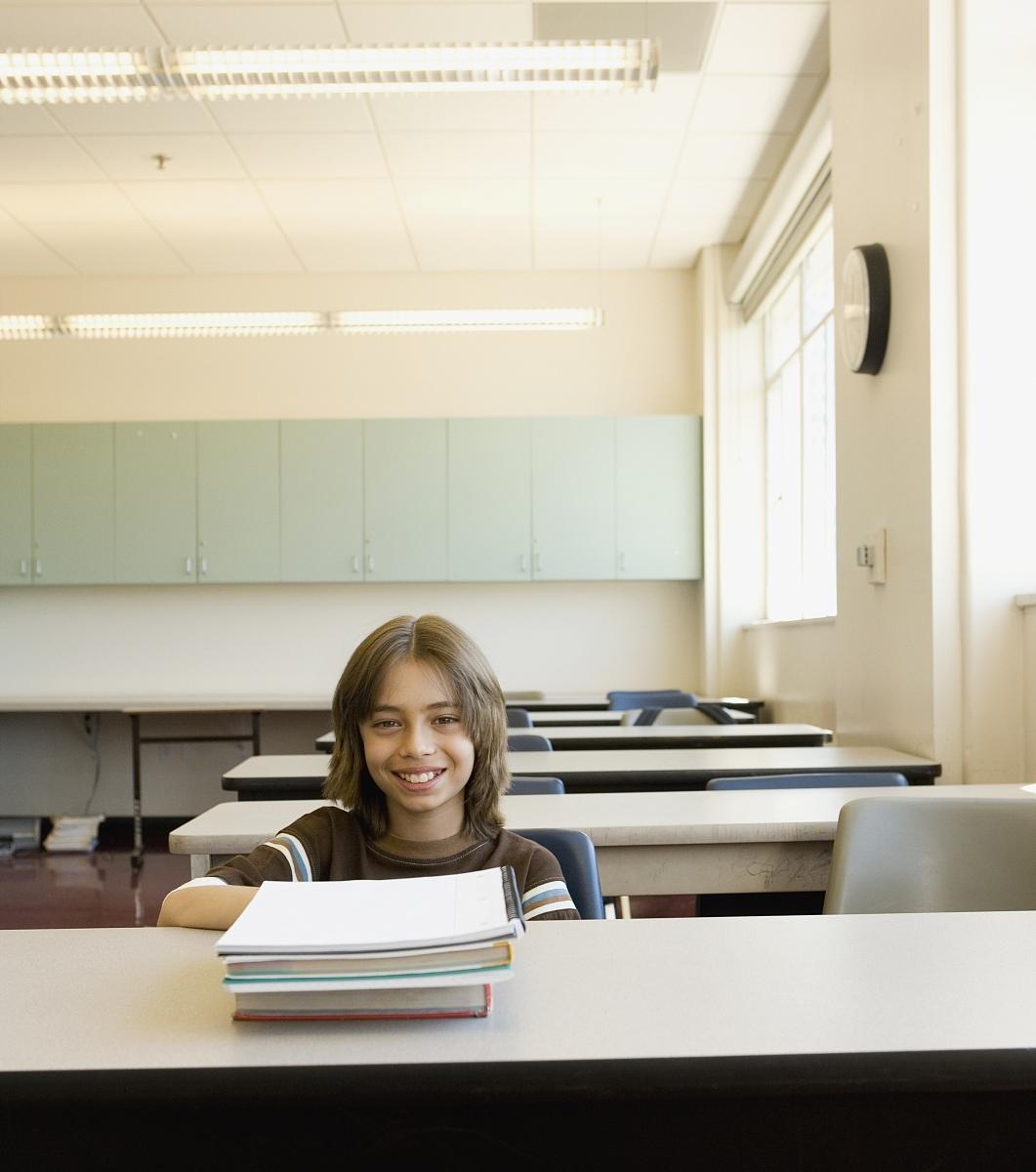 空教室里坐在课桌旁的男孩