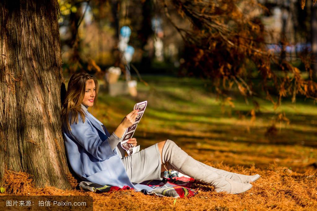 坐的_坐在秋天公园里的孕妇