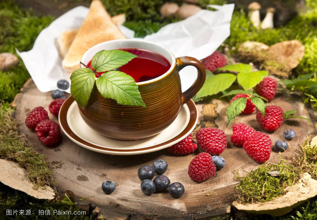树莓茶在树桩上的森林蘑菇和浆果图片
