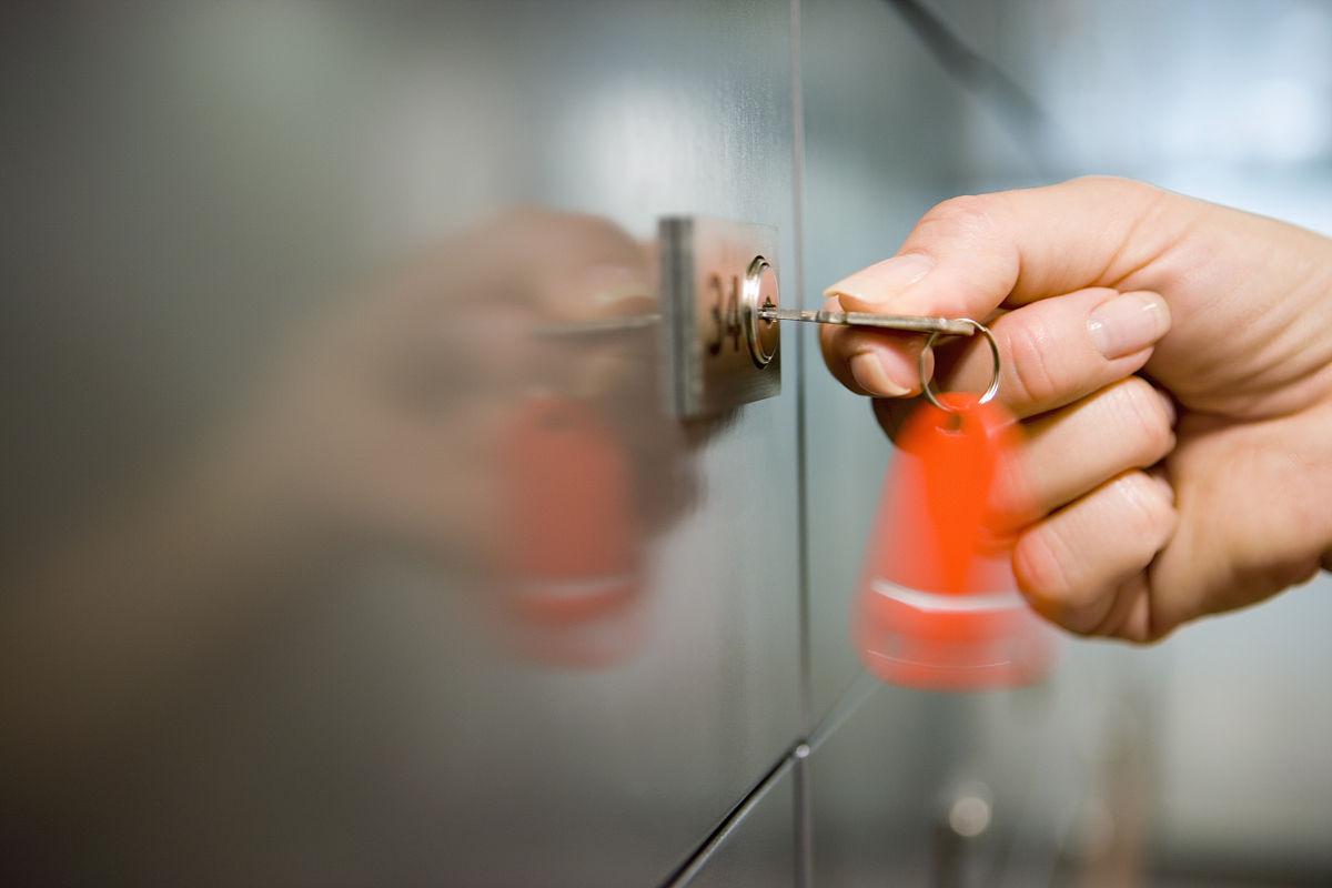 女子持有红色钥匙圈转动钥匙在门锁侧视图特写镜头(模糊运动)