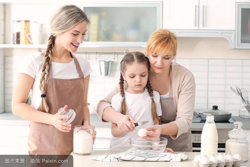 母亲和女儿在厨房做饭的年轻女子图片