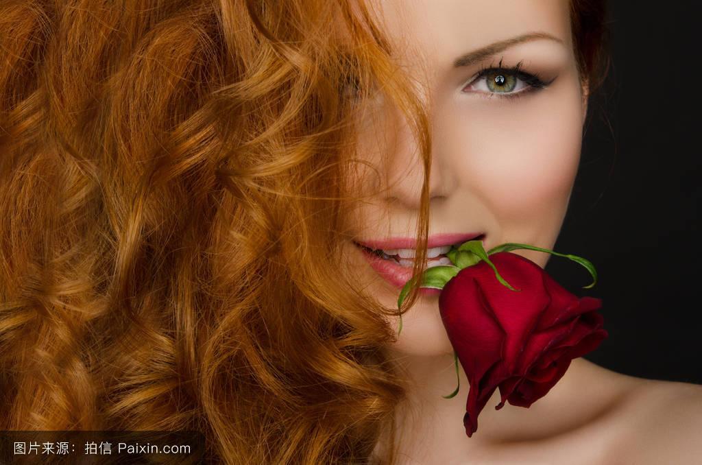 红头发的女人嘴里含着玫瑰花.图片