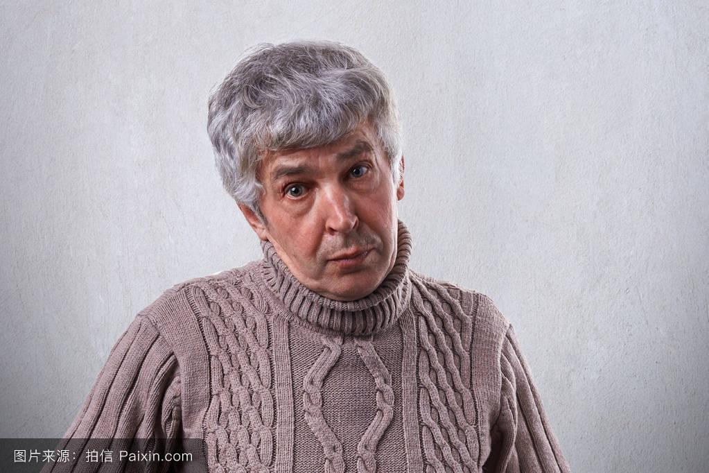 有皱纹的老男人,头发灰白,穿着毛衣,在白色背景下有同情的表情.图片