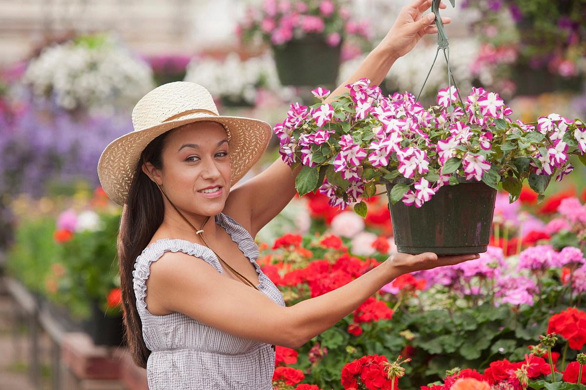在花园中心手捧鲜花的年轻女子