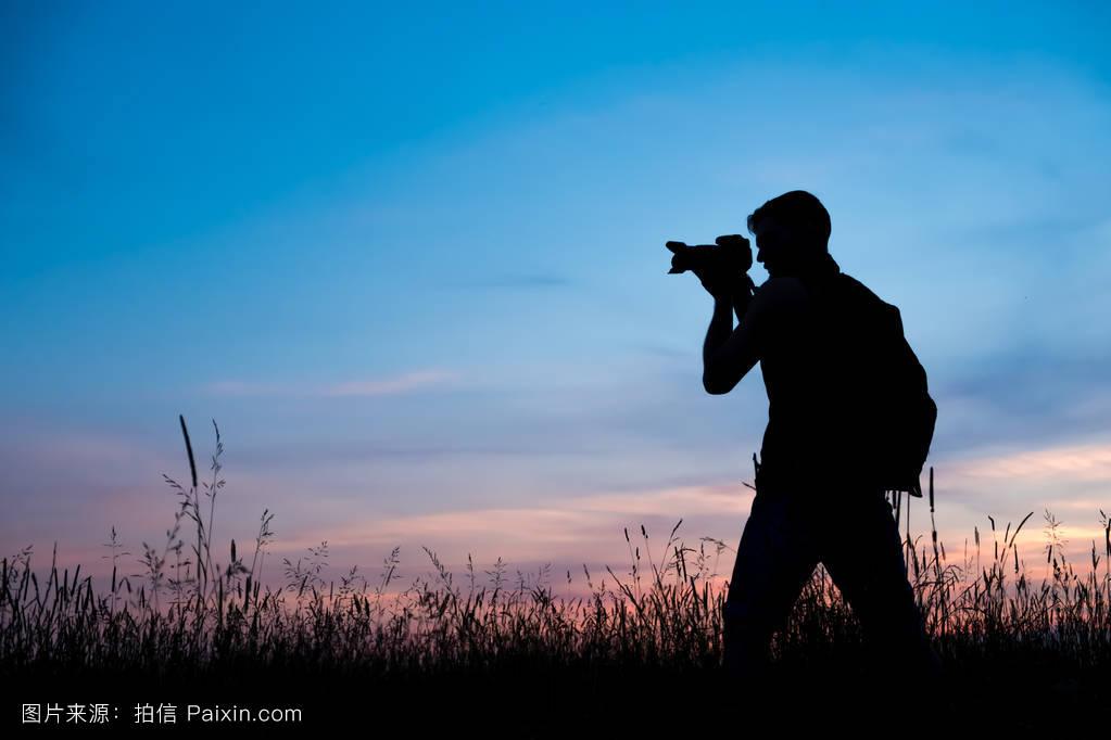 尹人摄影_一个喜欢旅行和摄影师的年轻人的剪影,拍摄日落,日出时美丽的瞬间.
