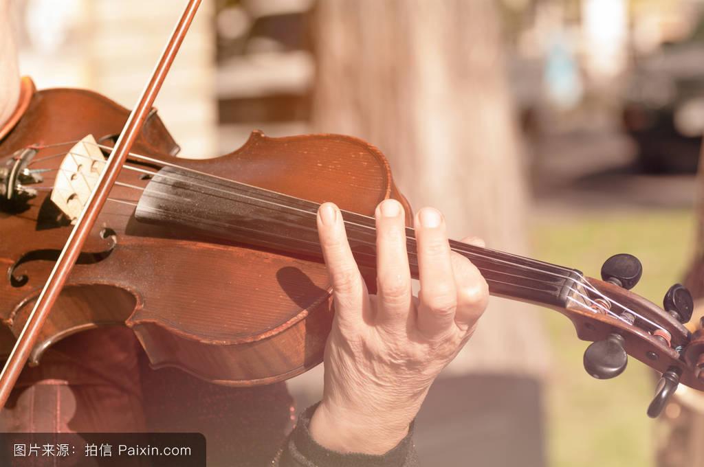 一个拉小提琴的女人的手图片
