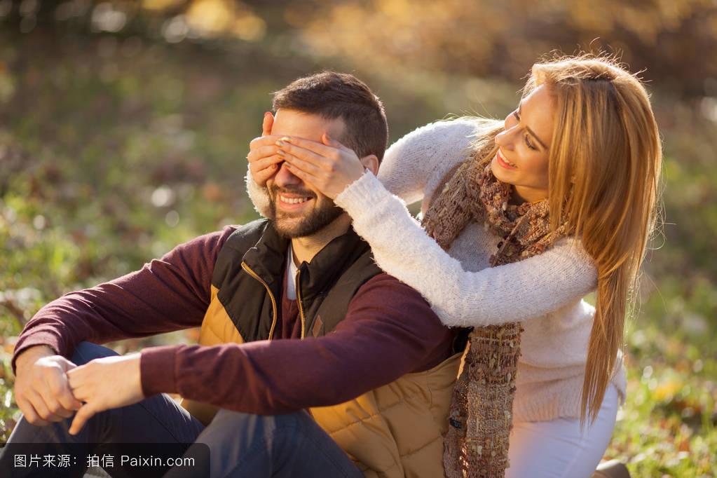 秋天公园里热烈的爱情.一对年轻的夫妇图片