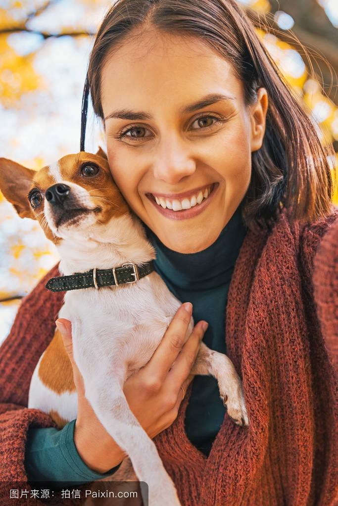 国内自拍偷拍性爱_微笑的年轻女子在秋天做户外的狗\