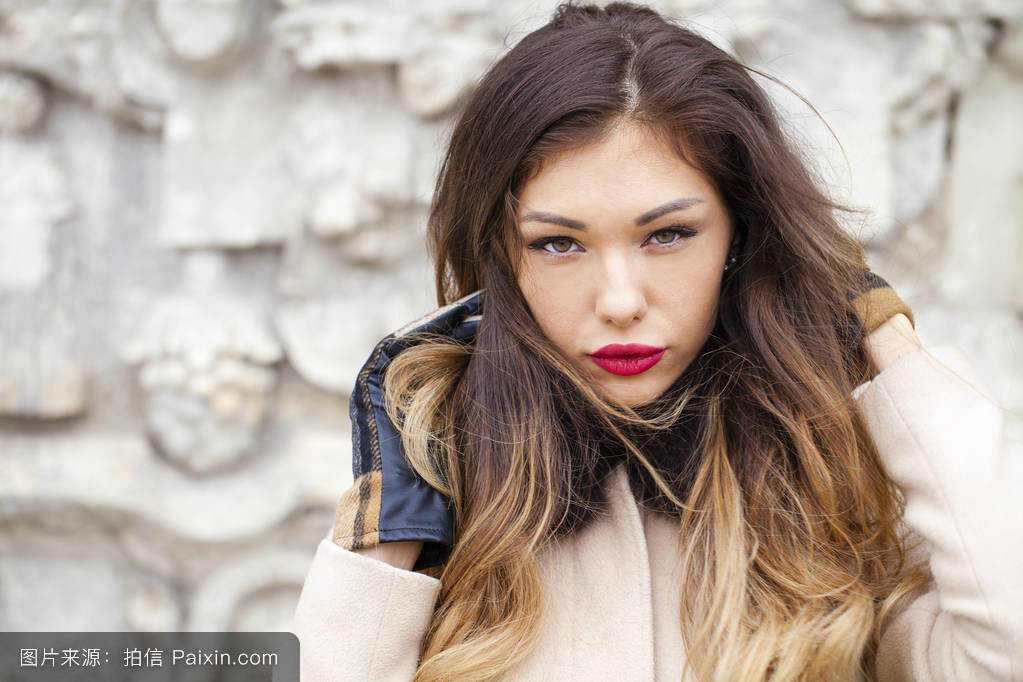 young beautiful woman in beige coat图片