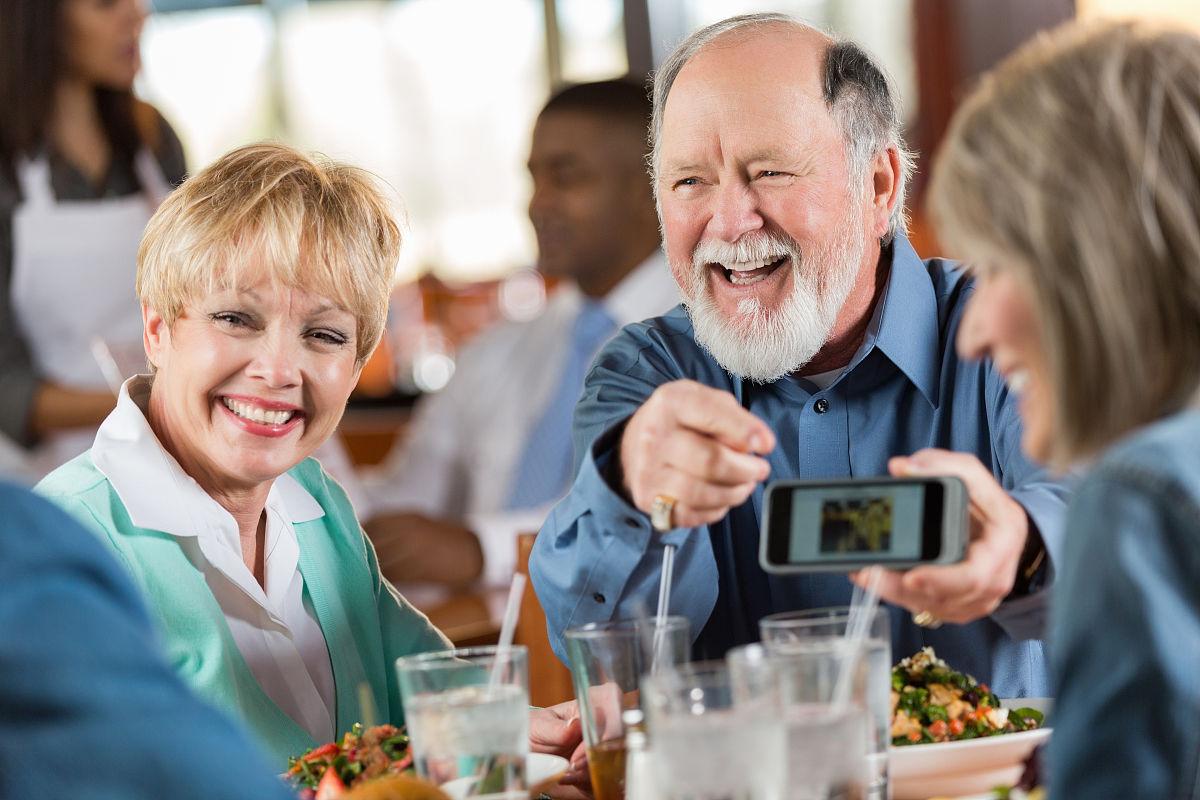 高级男男女女朋友一起吃饭笑
