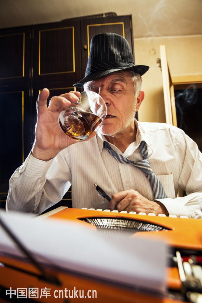 复古的高级作家喝了一杯威士忌