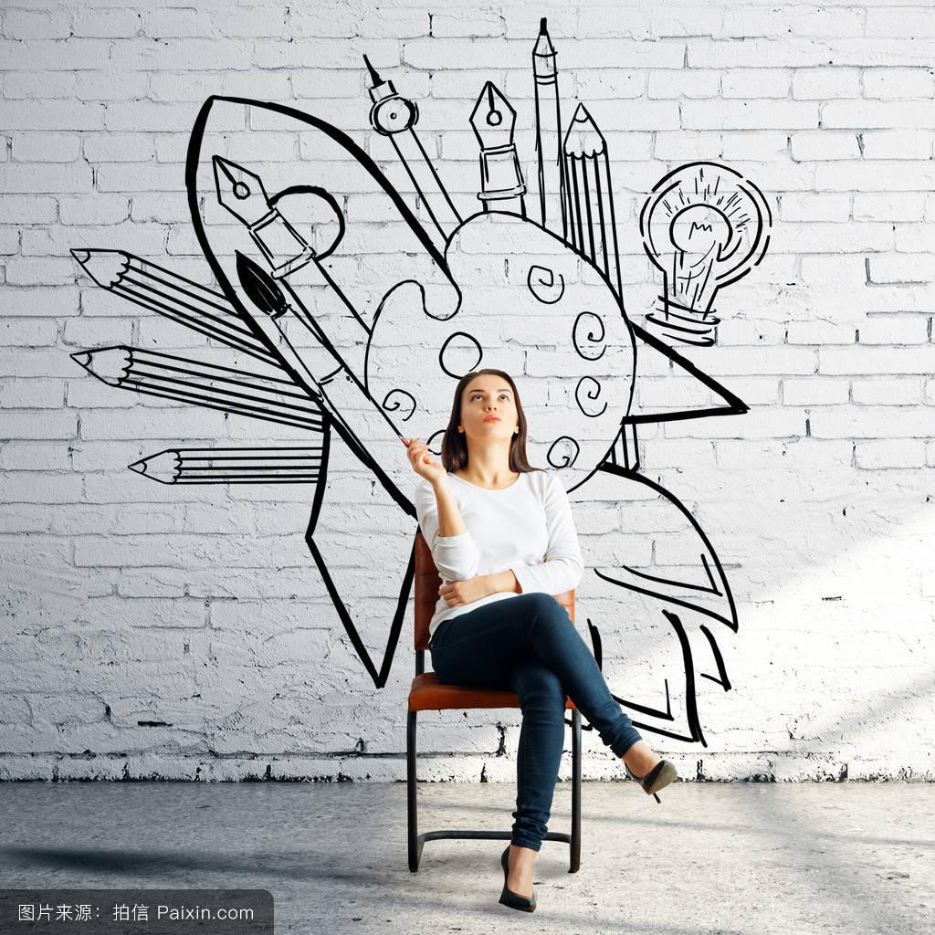 善解人意的女人在白色的bricj房间墙上有创意素描坐在椅子上.图片