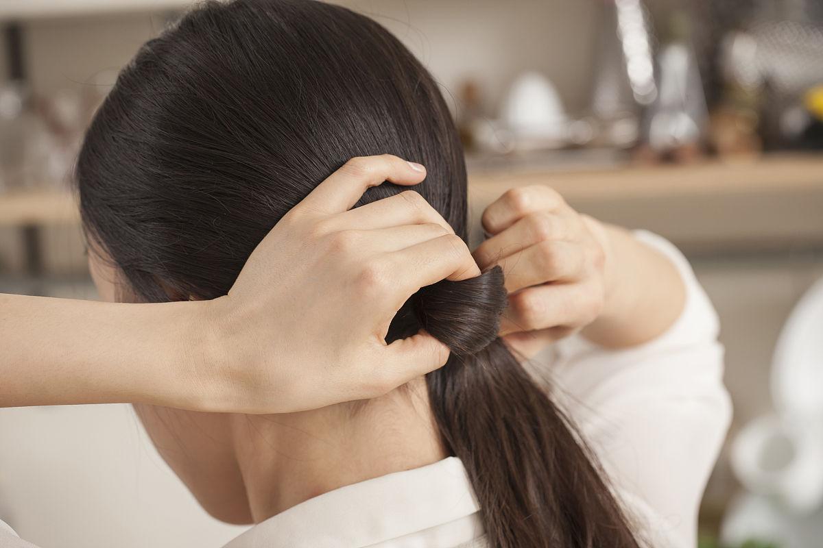 一个女人绑着她的头发图片
