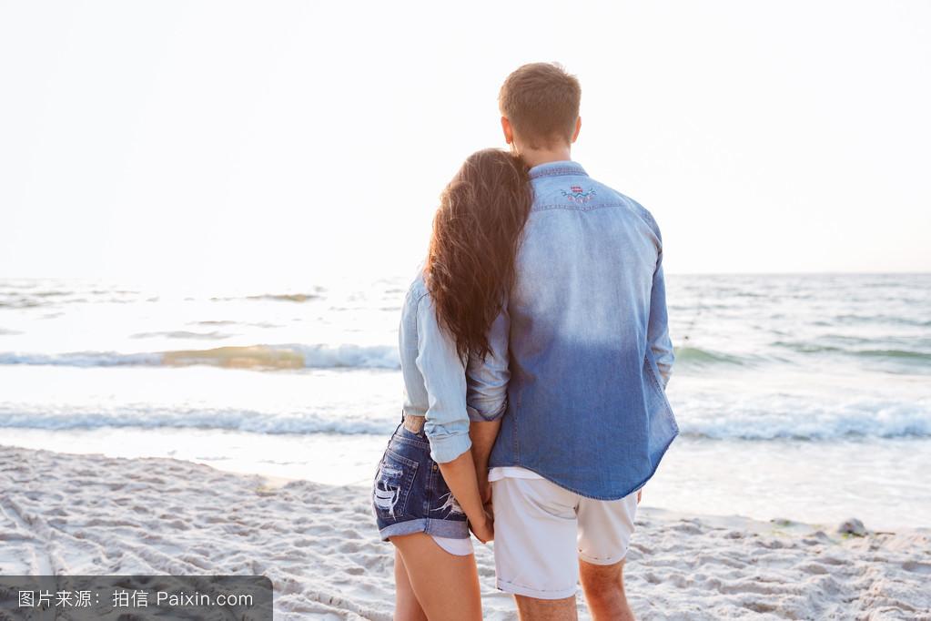 海滩上情侣站立和牵手的背影图片