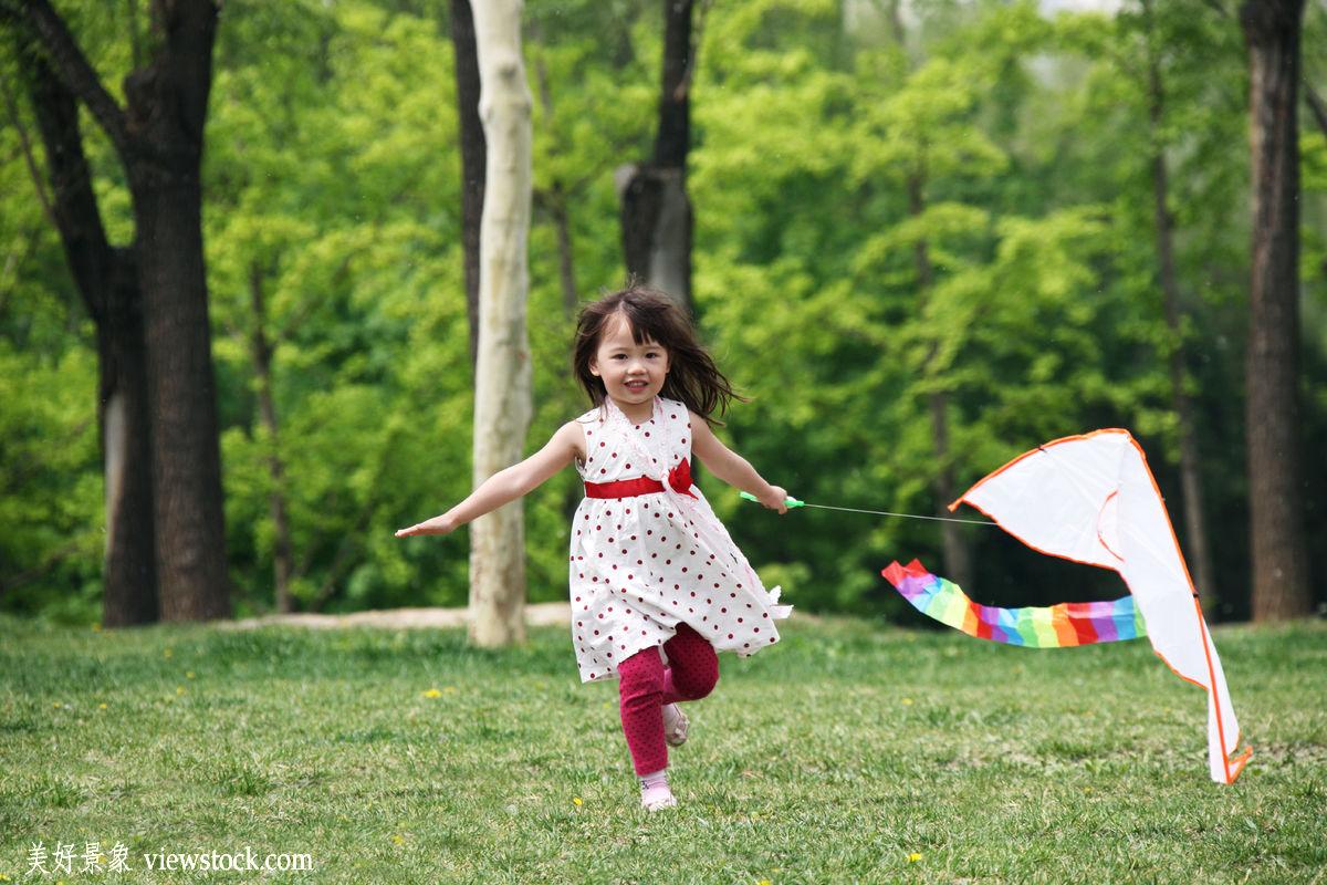 一个小女孩在户外放风筝图片图片