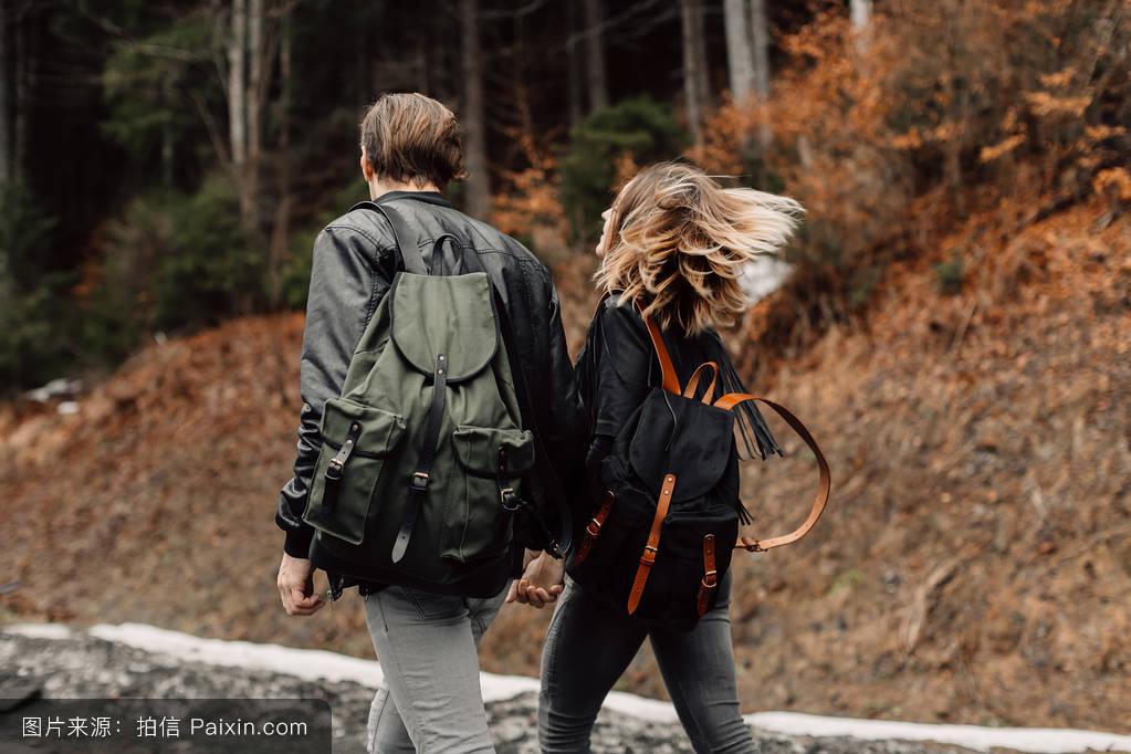 这对夫妇正在路上.背包背上的背包.飘动的头发随风飘动图片