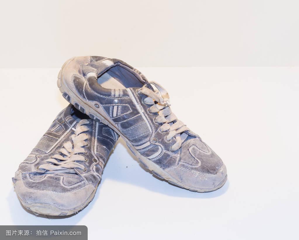 在浅色背景下系鞋带的很旧的跑鞋.图片