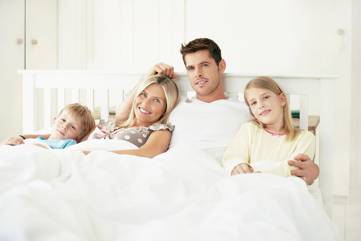带着孩子的中年夫妇在床上放松