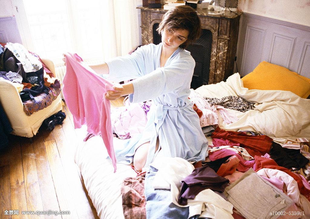 女人,跪着,床,堆放,衣服,拿着,向上,看,毛衣图片