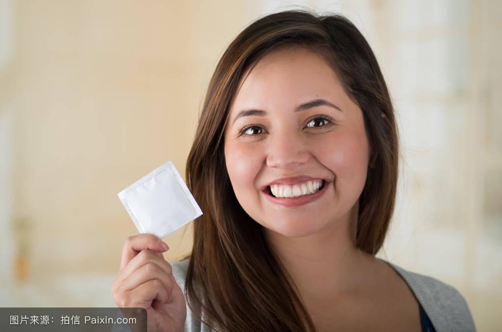 西西人用避孕套_年轻人拿着避孕套,面带微笑.帅