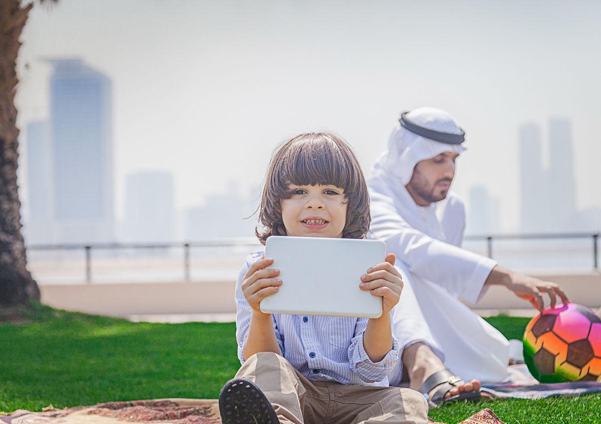小阿拉伯男孩在公園里使用數字平板電腦圖片