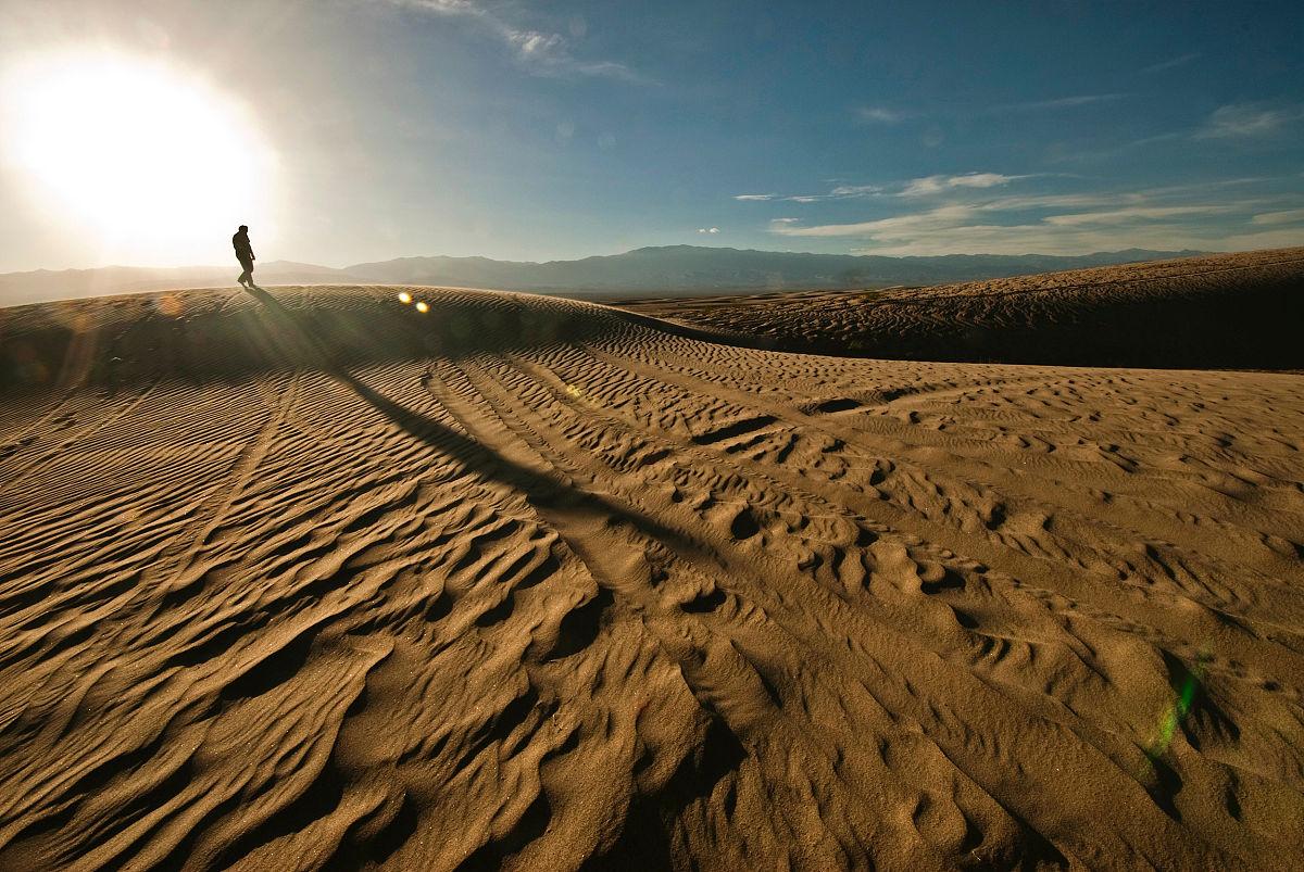 陽光明媚的沙漠中行走的人圖片